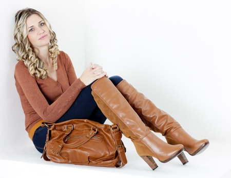 sitting woman wearing fashionable brown boots with a handbag photo