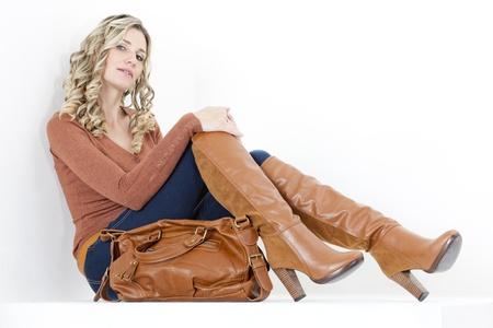 botas: mujer sentada vestida de moda botas marrones con un bolso