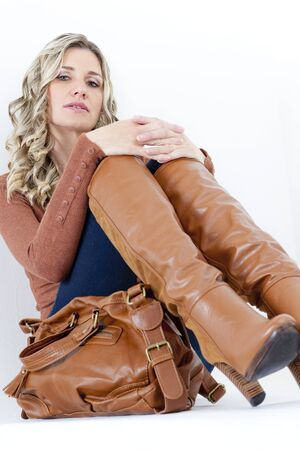 portrait of sitting woman wearing fashionable brown boots with a handbag Stock Photo - 15466685