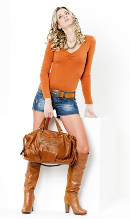 standing woman wearing fashionable brown boots with a handbag photo