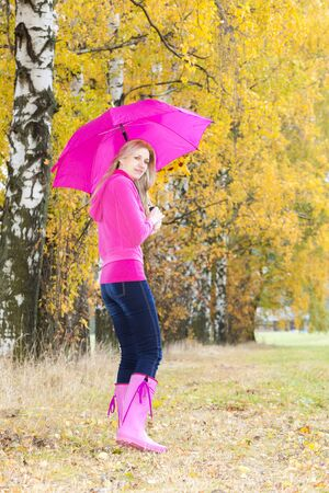 woman wearing rubber boots with umbrella in autumnal nature photo