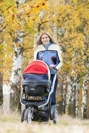 woman with a pram on walk in autumnal nature photo