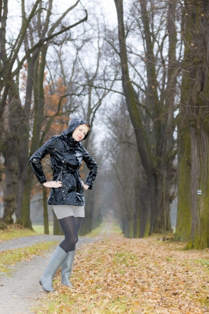 Frau mit Gummistiefeln in autumnal alley photo