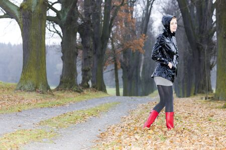 women in boots: woman wearing rubber boots in autumnal alley