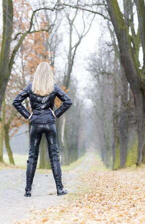 woman wearing black clothes and boots in autumnal alley photo