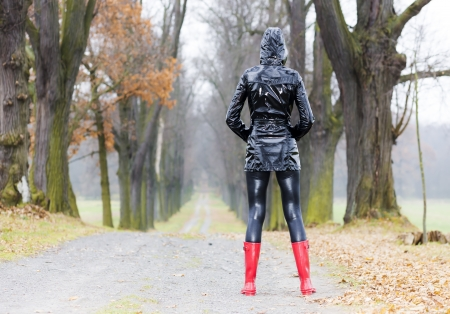 woman wearing rubber boots in autumnal alley