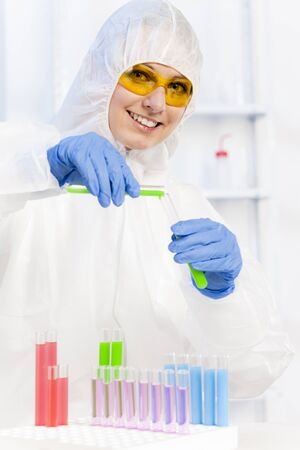 young woman wearing protective coat in laboratory photo