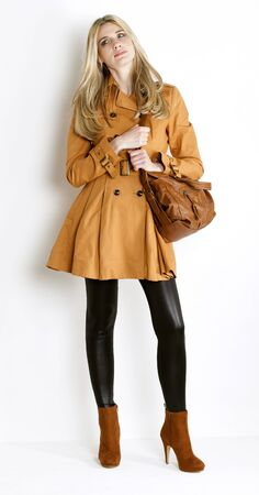 standing woman wearing coat and fashionable brown shoes with a handbag photo