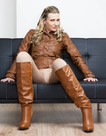 leather pants: woman wearing brown jacket and boots sitting on sofa