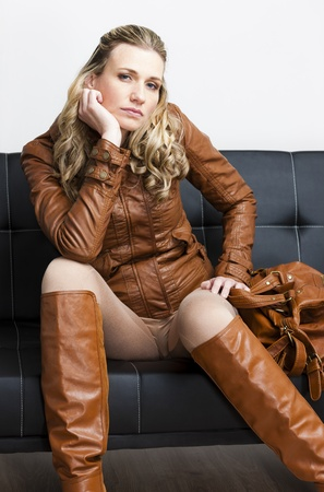 long pants: woman wearing brown jacket and boots sitting on sofa