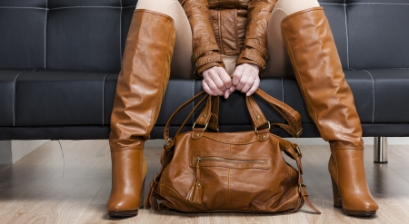 detail of sitting woman in brown clothes holding a handbag Stock Photo