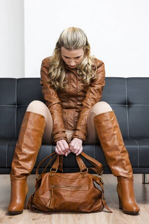 woman wearing brown jacket and boots sitting on sofa Stock Photo - 15466732