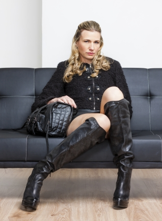 boots: woman wearing black clothes and boots sitting on sofa