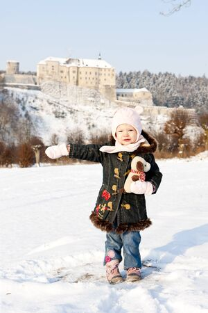 standing little girl and Cesky Sternberk Castle in winter at background, Czech Republic