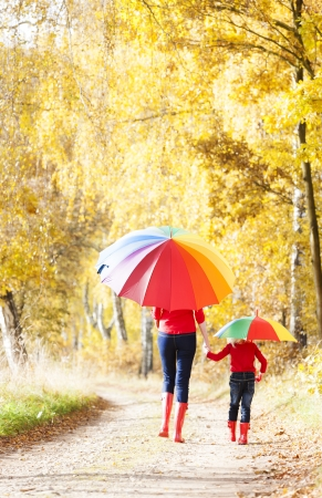 mother with her daughter with umbrellas in autumnal alley Foto de archivo