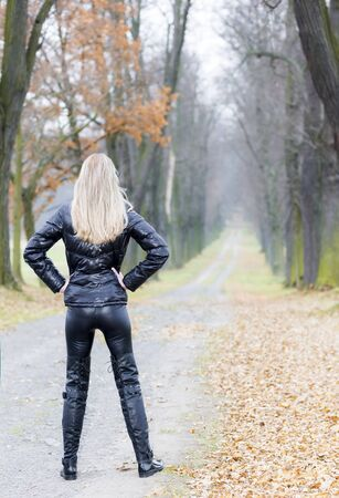 autumnal: woman wearing black clothes and boots in autumnal alley