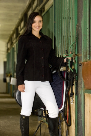 equestrian with saddle in a stable photo
