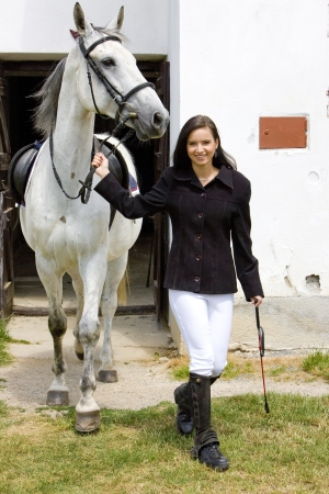 dark haired woman: equestrian with horse at stable