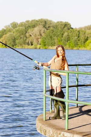 young woman fishing at pond photo
