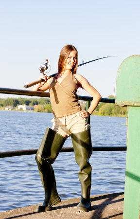 resting rod fishing: young woman fishing at pond