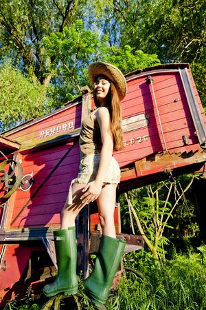 outside machines: young woman standing by old threshing machine