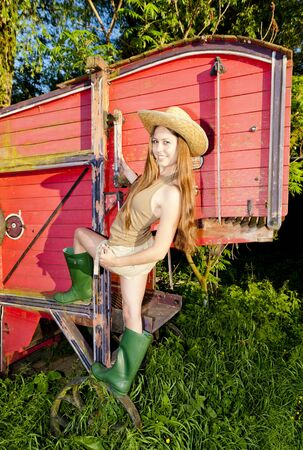 young woman standing by old threshing machine photo