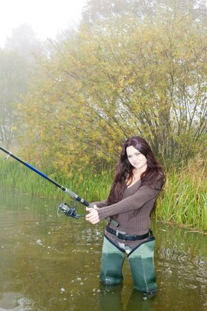 woman fishing in pond photo