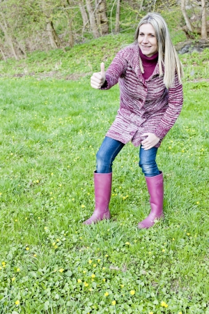 woman wearing rubber boots on spring meadow photo