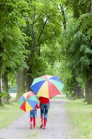 niños caminando: madre y su hija con paraguas en callejón primavera