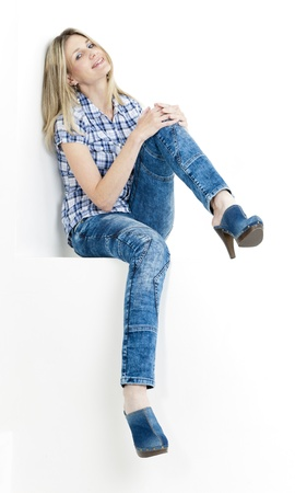 sitting woman wearing jeans and denim clogs photo