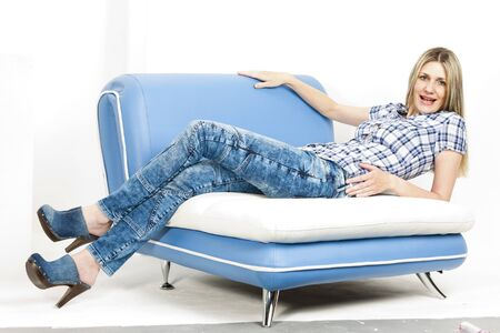 woman on sofa wearing jeans and denim clogs Stock Photo - 18604451