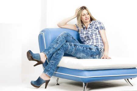 woman sitting on sofa wearing jeans and denim clogs photo