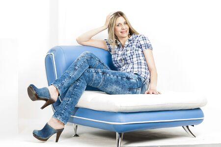 woman sitting on sofa wearing jeans and denim clogs Stock Photo - 18604212