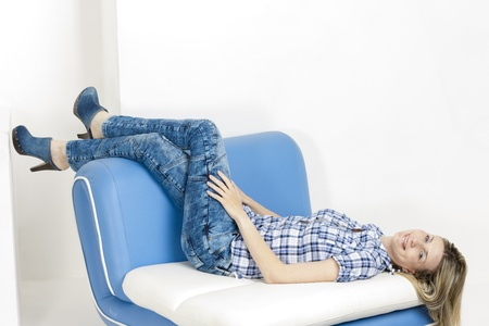 woman lying on sofa wearing jeans and denim clogs Stock Photo - 18604491