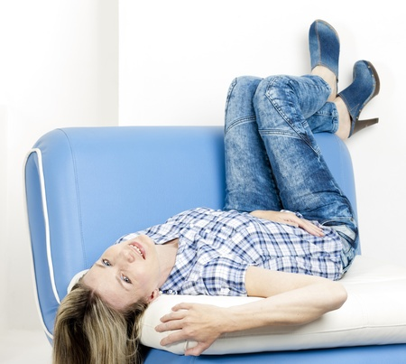 woman lying on sofa wearing jeans and denim clogs photo