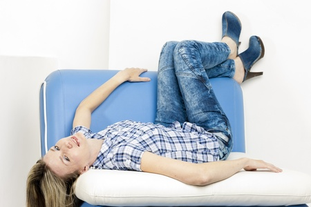 woman lying on sofa wearing jeans and denim clogs Stock Photo - 18604261