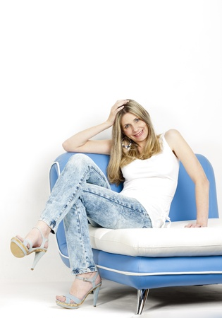 woman sitting on sofa wearing jeans and summer shoes Stock Photo - 18604433