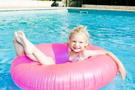 ni�as en bikini: ni�a con aro de goma en la piscina