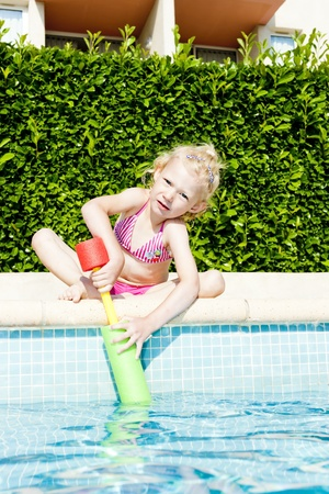 little girl with water sprayer by swimming pool photo