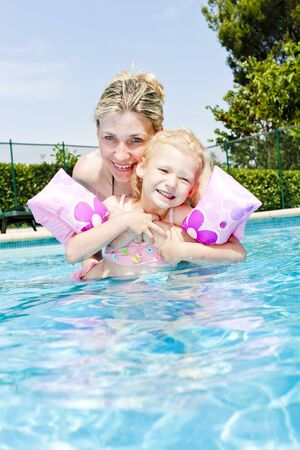 mother with her daughter in swimming pool photo
