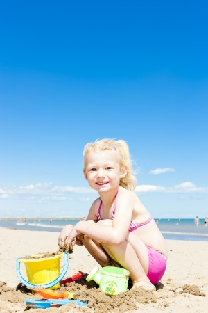 little girl playing on the beach at sea photo