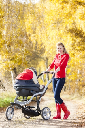 woman with a pram on walk in autumnal alley photo