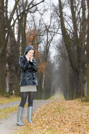 woman wearing rubber boots in autumnal alley photo