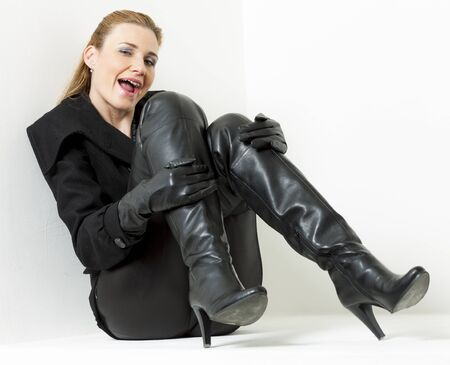 sitting woman wearing black clothes and boots photo