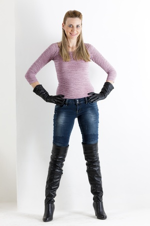 standing woman wearing jeans and black boots Stock Photo