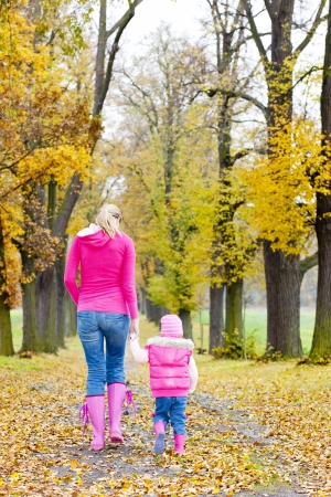 mother with her daughter in autumnal alley photo
