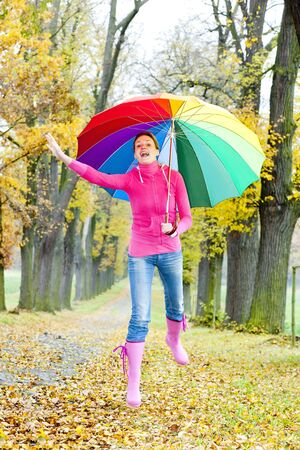 falltime: woman with an umbrella in autumnal alley Stock Photo