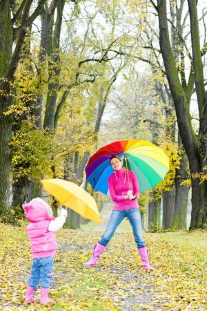 mother and her daughter with umbrellas in autumnal alley photo