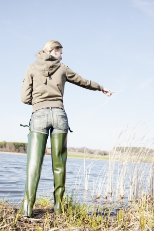 fisherwoman: woman fishing at a pond