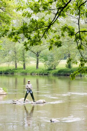 woman fishing in Sazava river, Czech Republic photo